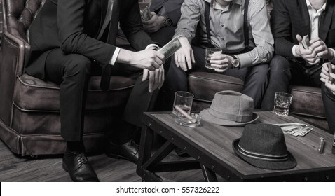 Whiskey, cigar and money on a table with gangster