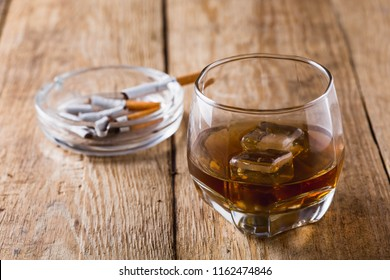 whiskey with cigarette on wooden table background