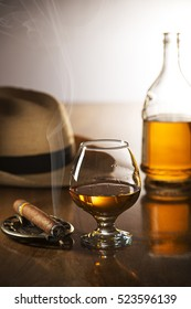 Whiskey, cognac, brandy and cigar on wooden background.