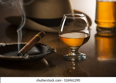 Whiskey, cognac, brandy and cigar on wooden background