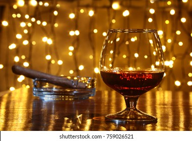 Whiskey, cognac, brandy and cigar on wooden table.