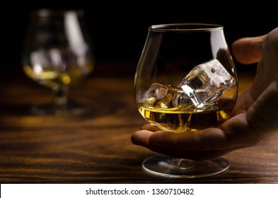 Whiskey / cognac glass with ice in a hand on a wooden background. Dark backdrop.