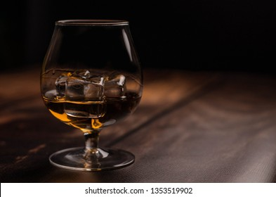 Whiskey / cognac glass with ice on a wooden background. Dark backdrop.