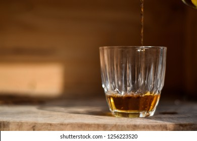 Whiskey drink being poured into a glass against wooden background.