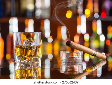Whiskey drink with smoking cigar on bar counter