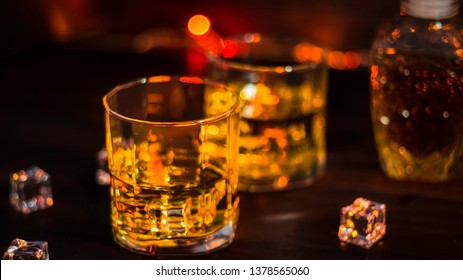 Whiskey in glass with beautiful amber ice, placed on a wooden table with a rough surface against a dark background and bokeh, with an alcoholic concept. drinks for celebrations and parties at night