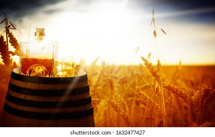Whiskey, glass and bottle on the barrel at the grain field in summer