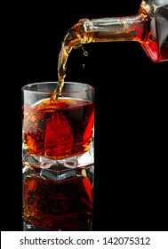 Whiskey glass and bottle on a black