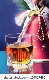 whiskey glass and christmas decoration red bell against color background