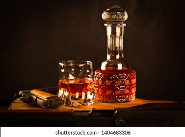 Whiskey glass drink with crystal carafe bottle near vintage colt pistol and thompson rifle near it on the wooden table