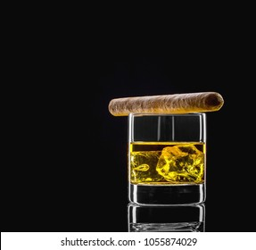 Whiskey glass with golden alcohol and cigar on black background