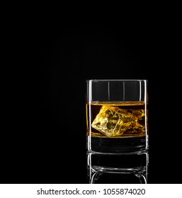 Whiskey glass with golden alcohol and ice cube on black background