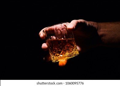 Whiskey glass in a hand of a man