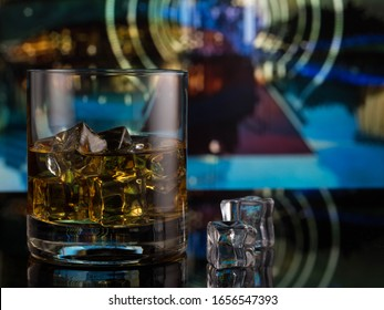 whiskey in a glass with ice on the background of the city night light blur bokeh