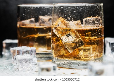 whiskey in a glass of ice on a black background. Alcoholic beverages