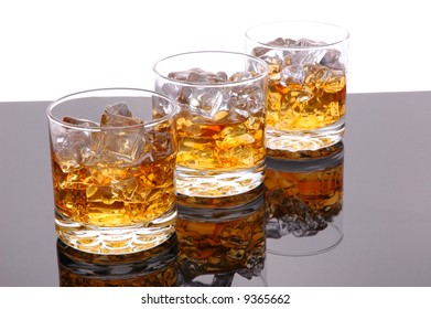 Whiskey in Glass of Ice with with reflection isolated over white