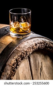 Whiskey glass and old wooden barrel