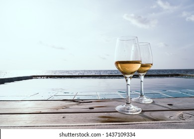whiskey glass with swimming pool and sea background - selective focus point