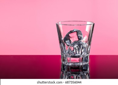 whiskey glasses with ice cubes isolated on pink background