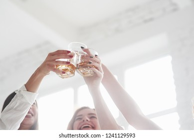 Whiskey glasses into the air. Girls having party with alcohol.