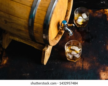 Whiskey glasses on a black background and a wooden barrel