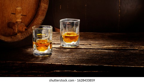 Whiskey glasses stand on a wooden table next to a whiskey barrel, still life in the distillery
