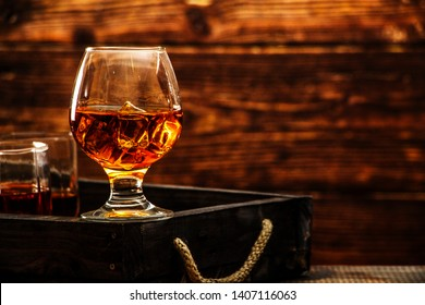 Whiskey with ice or brandy in a glass and a square carafe on an old wooden background. Whiskey with ice in a glass. Whiskey or cognac. Selective focus.