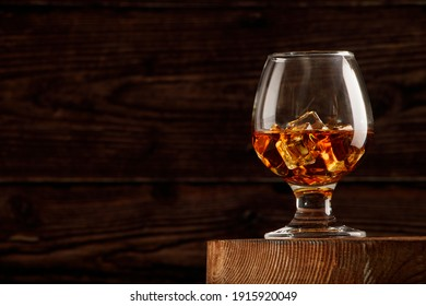 Whiskey with ice or brandy or rum in glass on rustic background. Whiskey with ice in a glass. Whiskey or brandy. Selective focus. Rum with ice on wooden background.