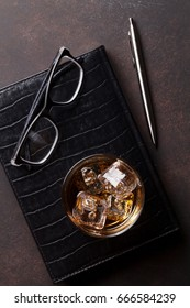 Whiskey with ice and business office supplies. Top view