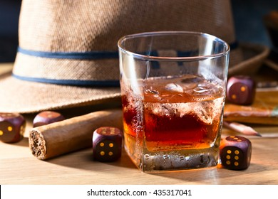 whiskey with ice and cigar on wooden table