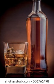 whiskey with ice cubes in glass near bottle on black background, warm atmosphere, time of relax with whisky