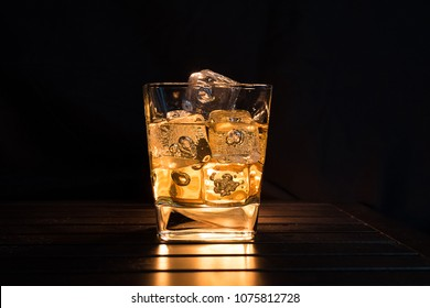 whiskey with ice cubes in glass on dark background and wood table, relax with whisky concept on the warm atmosphere