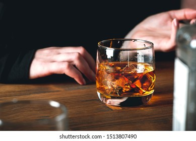 Whiskey with ice cubes in a glass on a wooden tabletop in a pub, dark background. Woman drinks whiskey at the bar.