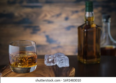 Whiskey and ice cubes and two bottles with brandy or scotch on wooden background with copy space
