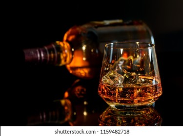 Whiskey with ice in glass and a bottle of whiskey on black background.