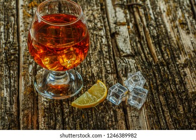 Whiskey with ice in a glass on an old dark tree table. Whiskey or cognac on a wooden dark table. Whiskey. Selective focus.