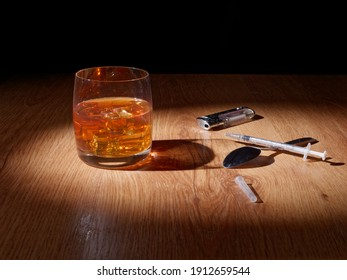 Whiskey with ice in a glass glass, pills and drugs are nearby, the concept of the harm of alcohol and drugs on the human body
