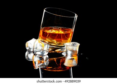 whiskey with ice in an inclined beaker on a black background with reflection