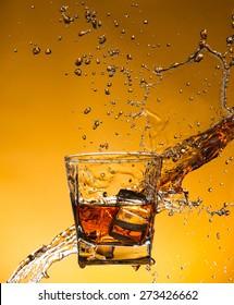 Whiskey with ice with liquid splash, freeze motion.
