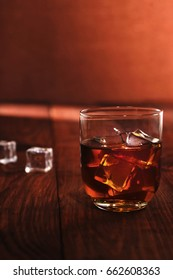 whiskey with ice on a brown background