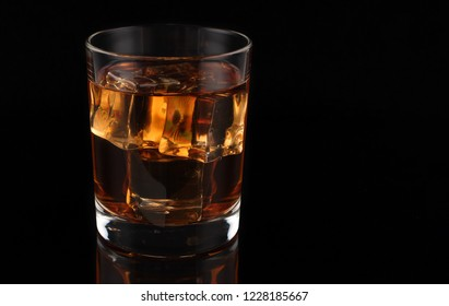 Whiskey with ice on a dark background