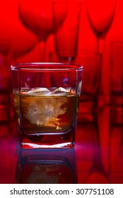 whiskey with ice on glass table in bar