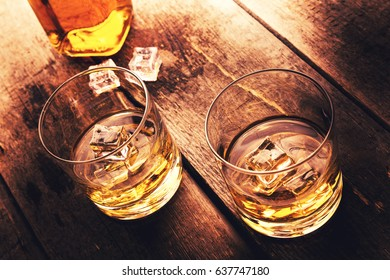 whiskey with ice on old dark wooden table