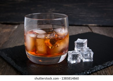 Whiskey with ice on wooden table.