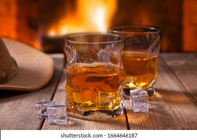 whiskey with ice on a wooden table with fireplace and cowboy hats on the background