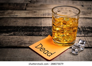Whiskey in light pool and dead note on brown table