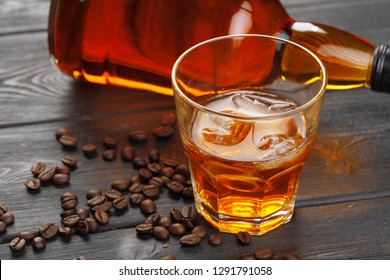 Whiskey or liqueur, coffee beans and orange cut on wooden background. Seasonal holidays concept.