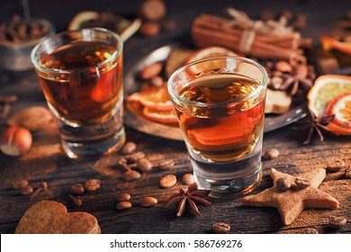 Whiskey or liqueur, cookies, spices and decorations on wooden background. Seasonal holidays concept.