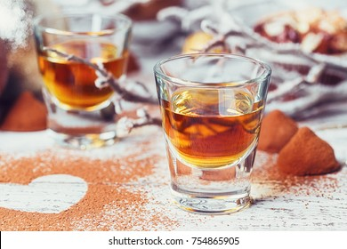 Whiskey or liqueur, truffle chocolate candies in cocoa powder and christmas decorations on white wooden background. Seasonal holidays concept. Winter and New Year background.