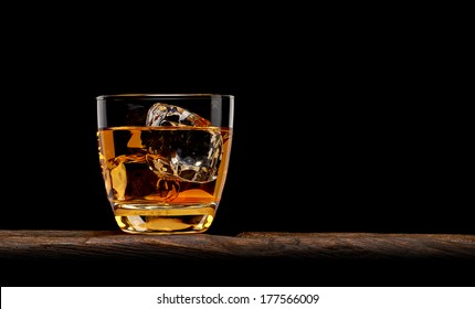 Whiskey or manhattan cocktail with ice cubes in rocks glass on wooden table